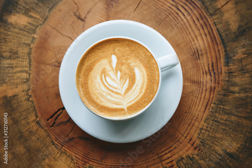 Close up of fresh aromatic cappuccino coffee on a wooden surface. Fotobehang