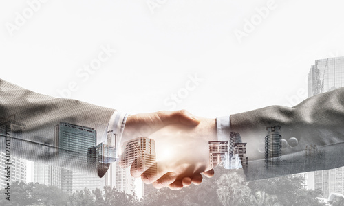 Photo Business handshake as idea for unity and cooperation or greeting