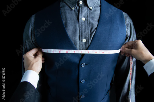 Valokuva The dressmaker was measuring the chest width of a man wearing a blue suit