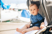 Outdoor Portrait Of Adorable Baby Boy Sitting In A Stroller