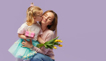 8 March Card! Little Daughter Kisses And Hugging Her Mother With Yellow Flowers Tulip And Gift Box. Purple Studio Background. Mothers Day Concept