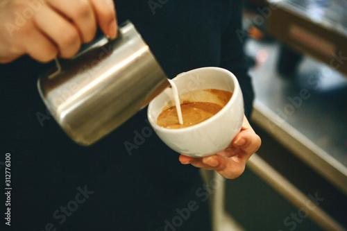 Obraz Barista pours milk or cream into coffee - fototapety do salonu