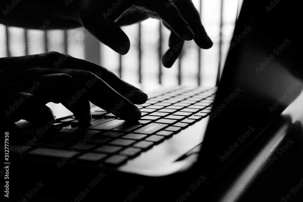 Fototapeta hacker or cyber crime hand reaching, stealing information on laptop, attack signifying internet theft while using online banking, anonymous business in technology internet and networking concept
