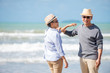 Relax asian senior couple on beach with blue sky background
