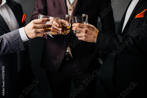 Photo Close-up partial view of three friends clink glasses of whiskey drink, alcoholic beverage