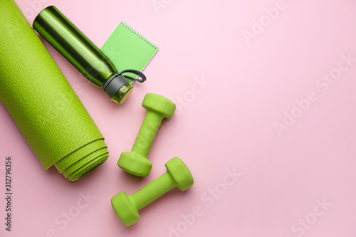 Obraz Dumbbells with notebook, yoga mat and bottle of water on color background - fototapety do salonu