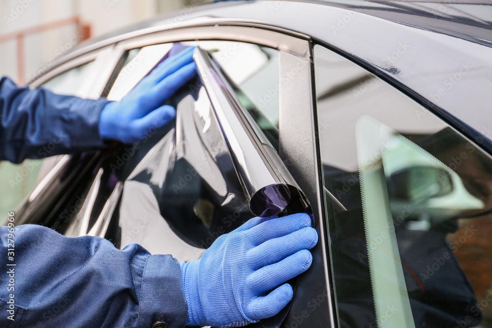 Fototapeta Male worker tinting car window