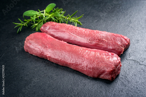 Fotografie, Tablou Raw dry aged venison tenderloin fillet steak natural with herbs offered as close