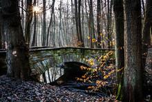 A Stone Bridge Over A Creek Wi...