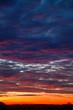 Leinwandbild Motiv Beautiful sunrise: orange, red and dark blue clouds over a black horizon