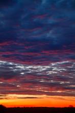 Beautiful Sunrise: Orange, Red And Dark Blue Clouds Over A Black Horizon
