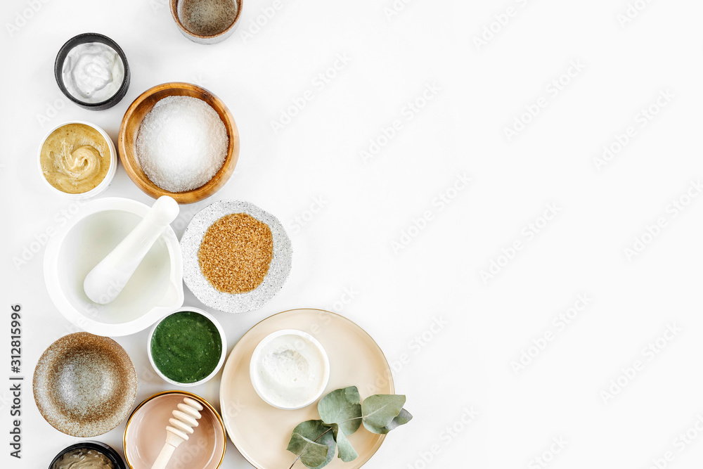 Fototapeta Beauty treatment ingredients for making homemade skin care cosmetic mask. Various bowl with clay, cream, essential oil and natural ingredients  on white table background. Organic spa cosmetic products