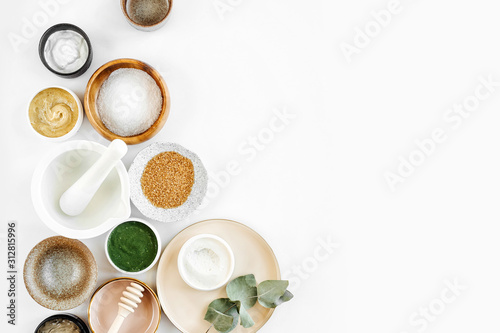 Fototapeta Beauty treatment ingredients for making homemade skin care cosmetic mask. Various bowl with clay, cream, essential oil and natural ingredients  on white table background. Organic spa cosmetic products obraz