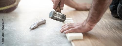 Fotomural Hammer und Schlagholz im Einsatz beim Bodenlegen