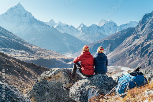 Obraz Couple resting on the Everest Base Camp trekking route near Dughla 4620m. Backpackers left Backpacks and trekking poles and enjoying valley view with Ama Dablam 6812m peak and Tobuche 6495m - fototapety do salonu