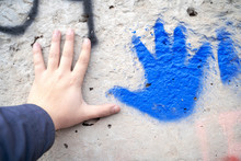 Human Hand And Bright Blue Pal...