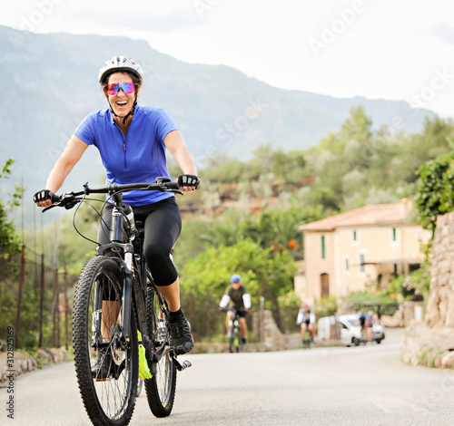 Fotografia Woman riding an E Bike up a hill in Mallorca.