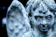 Death. Angel Against Black Background. Fragment Of Ancient Statue.