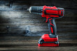 Leinwanddruck Bild - red cordless drill driver electric screwdriver on vintage wood background