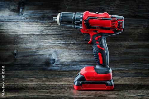 Fotografia red cordless drill driver electric screwdriver on vintage wood background