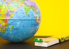 Matchstick And World Globe On A Yellow Background, Concept Of Saving The Planet From Fire