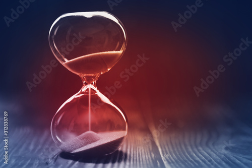Obraz na plátne  Modern Hourglass with dark background, sand trickling through the bulbs of a crystal sand glass, with red light in the center