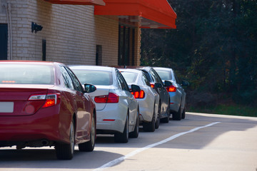 Generic drive thru pickup window with cars waiting in line to get their products or food