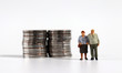 canvas print picture A miniature old couple standing next to a pile of coins.