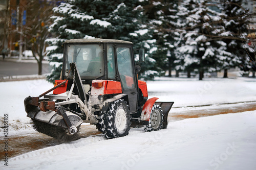 Tractor cleaning sidewalk from snow with snow plow and rotating brush Canvas Print