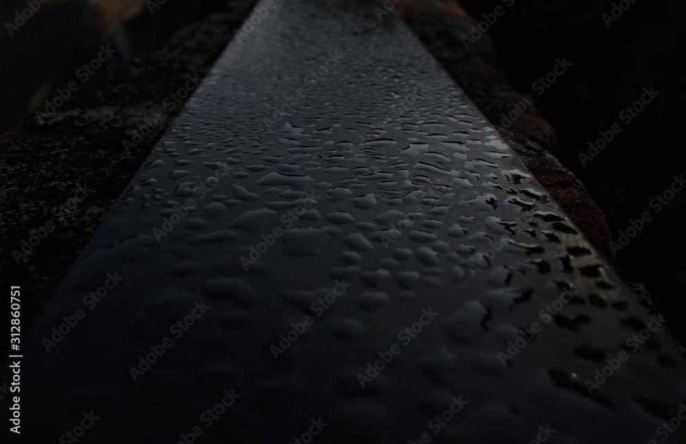 Fototapeta Dew droplets on a dark granite slab at dawn