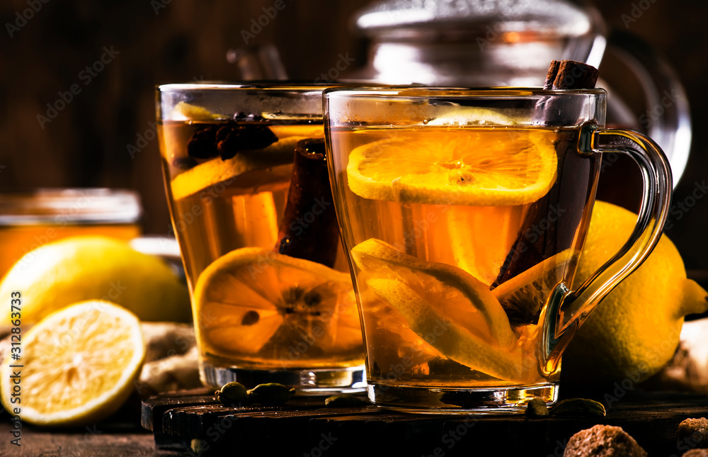 Fototapeta Hot healing tea with ginger, honey, lemon and spices in glass cup, rustic wooden background copy space