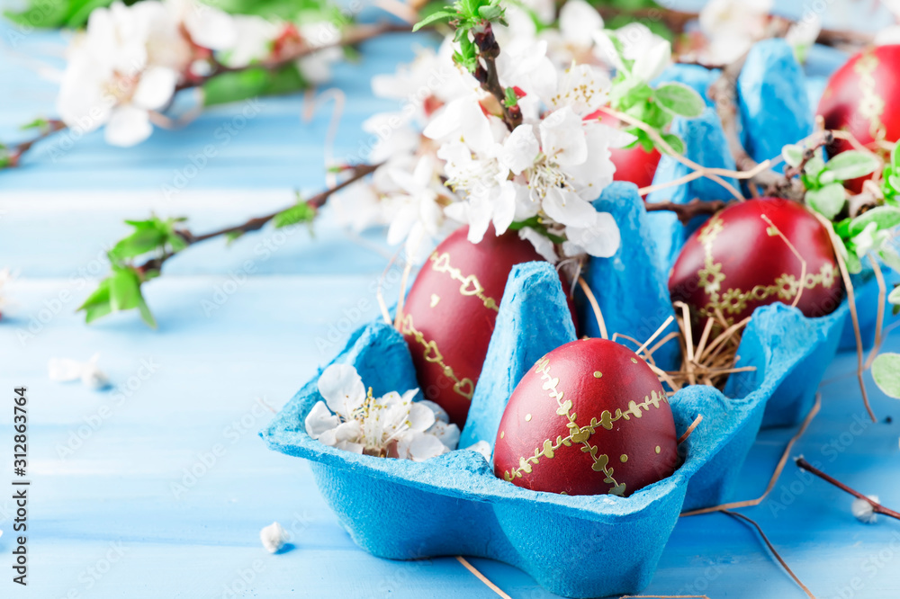 Fototapeta Easter eggs and spring white flowers on Easter blue background with copy space