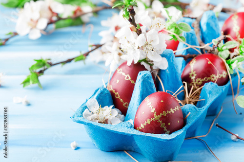Obraz Easter eggs and spring white flowers on Easter blue background with copy space - fototapety do salonu