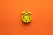 canvas print picture - Yellow alarm clock on the middle of orange background