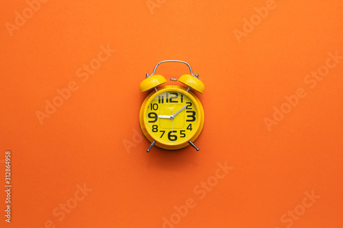 Yellow alarm clock on the middle of orange background Obraz na płótnie