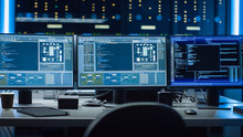 Shot Of Multiple Personal Computer Monitors Showing Coding Language Program With System Monitoring Interface. In The Background Data Center With Server Racks.