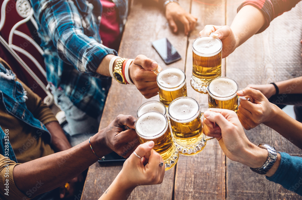 Fototapeta Group of people enjoying and toasting a beer in brewery pub - Friendship concept with young people having fun together