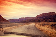 Driving A Car On A Mountain Road In The Desert. View Of Sandstone Mountains Through The Windscreen. Timna Park, Israel