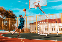 Sports And Basketball. A Young Teenager In A Blue Tracksuit Jumps And Throws A Ball Into The Basket. Blue Sky And School In The Background