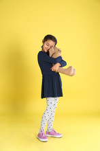 Cute Little Girl With Toy Bunny On Yellow Background
