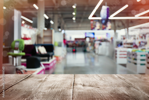 Fotomural Empty wooden surface and blurred view of furniture store in mall