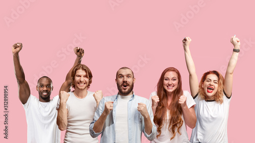 Obraz Portrait of multiethnic group of young people isolated on pink studio background, flyer, collage. Concept of human emotions, facial expression, sales, advertising. Celebrating, winning, happy. - fototapety do salonu