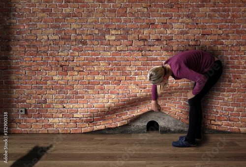 Fototapeta Frau hebt Mauer wie einen Vorhang an und deckt Mauseloch auf