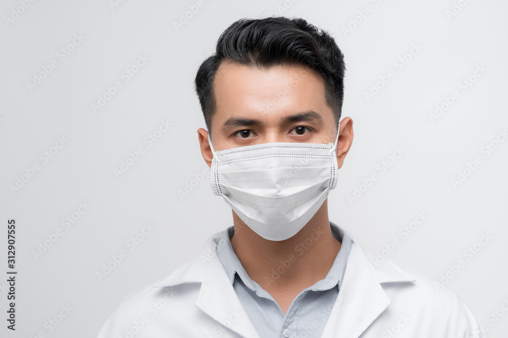 Fototapeta Handsome doctor portrait with a white coat, face mask