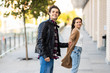 Happy to be together. Beautiful young couple holding hands and looking at each other with smile while walking through the city street