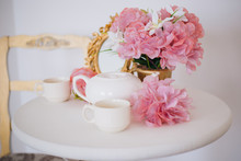 Tea Table, Mugs And A Teapot White Teapot With A Pink Bouquet Of Flowers In The Rococo Style. Golden Vintage Mirror. White Pink Eltion Interior