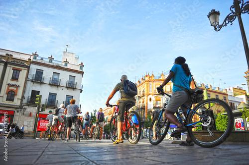 Fotografie, Obraz Tourists on bike tour through Triana neighborhood in Seville, Andalusia, Spain