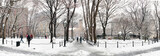 Fototapeta Nowy Jork - Panoramic winter scene with people walking through the snow covered landscape of Washington Square Park in New York City