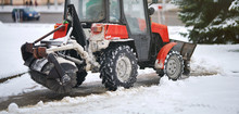 Red Tractor Clearing Snow On F...