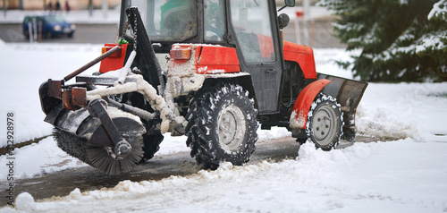 Fotografiet  Red tractor clearing snow on footpath, with snow plow and rotating brush